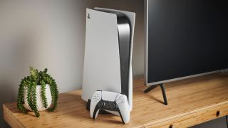 best TV for PS5: Person holding the PlayStation 5 DualSense controller in front of a TV