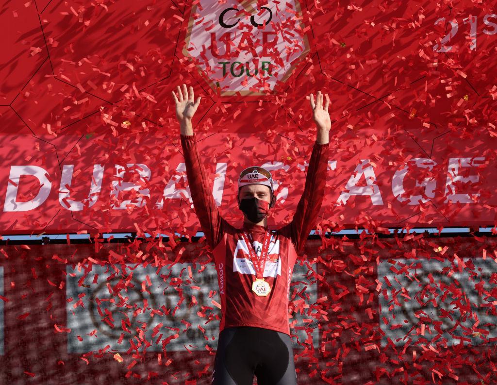 Race leader Tadej Pogacar of Team UAE Emirates celebrates on the podium after the sixth stage of the UAE Cycling Tour From Dubai Deira Islands to Dubai Palm Jumeriah on February 26 2021 Photo by Giuseppe CACACE AFP Photo by GIUSEPPE CACACEAFP via Getty Images