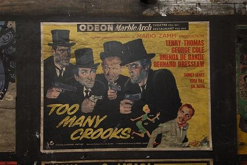Vintage film poster for British comedy Too Many Crooks. Photo taken in a disused passageway of Notting Hill Gate station by Mike Ashworth of London Underground.