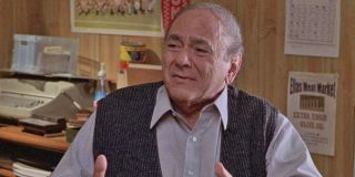 Michael Constantine looks concerned, sitting at his desk, in My Big Fat Greek Wedding.