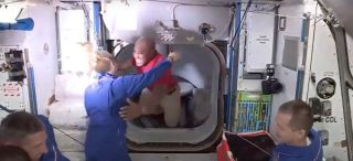 "Victor Glover (center) hugs fellow NASA astronaut Kate Rubins just after floating aboard the International Space station from the SpaceX Crew Dragon capsule ""Resilience"" early on the morning of Nov. 17, 2020."