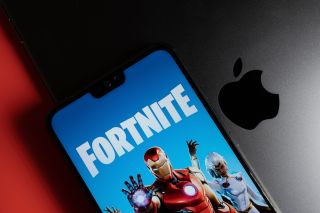 Fortnite vs Apple. Game login screen from Epic Games seen on the smartphone placed on ipad. Epic Games vs Apple lawsuit concept.