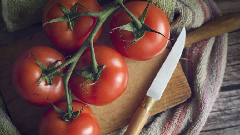 ripe tomatoes on a chopping board