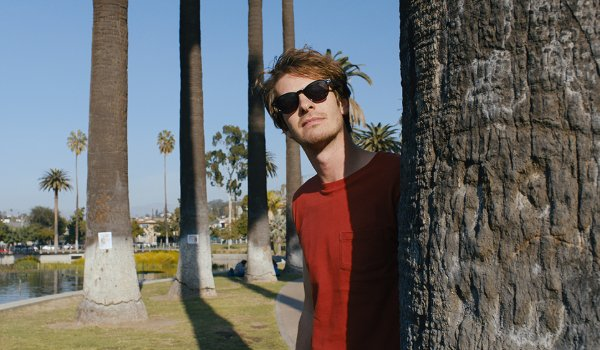 Under The Silver Lake Andrew Garfield wearing sunglasses in the park