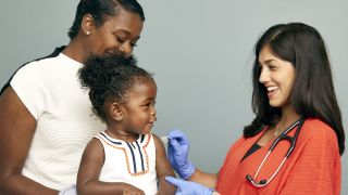 A smiling doctor prepares to deliver a vaccine to a happy toddler.