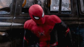 Spider-Man (Tom Holland) hides behind a car in Spider-Man: Far From Home