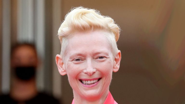 """British actress Tilda Swinton (L) and Us actor Adrien Brody smile as they arrive for the screening of the film """"The French Dispatch"""" at the 74th edition of the Cannes Film Festival in Cannes, southern France, on July 12, 2021. (Photo by Valery HACHE / AFP) (Photo by VALERY HACHE/AFP via Getty Images)"""