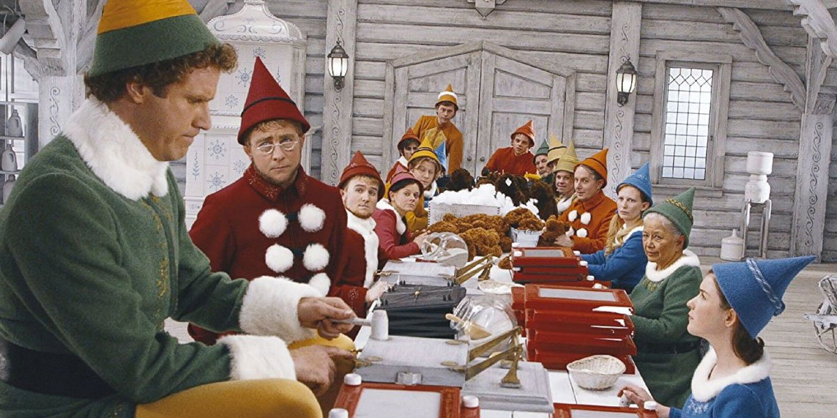 Will Ferrell sitting at a table with elves and looking gigantic.