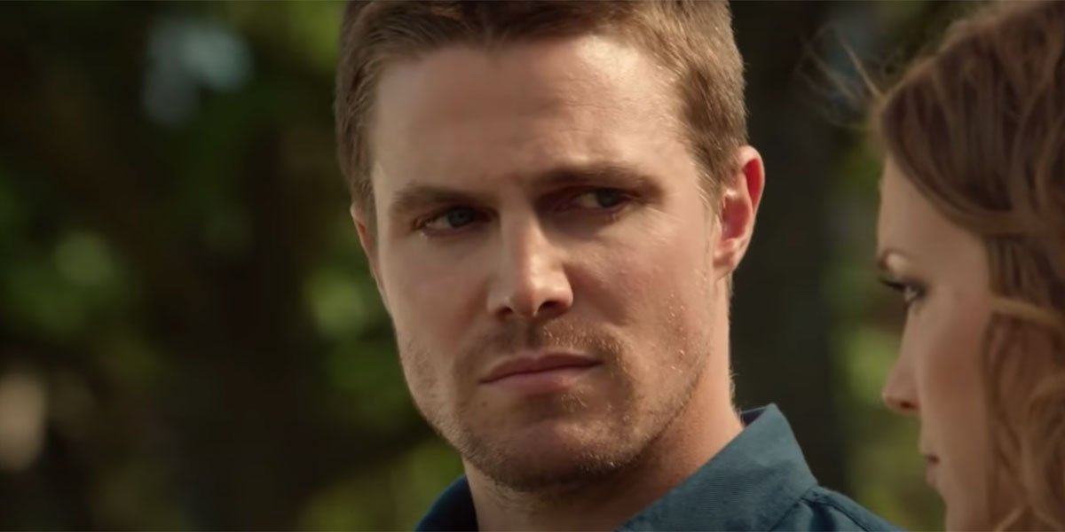Arrow's Stephen Amell sitting on a park bench and having a conversation, looking solemn.