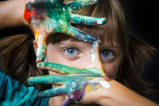 A young girl with watercolor on her hands.