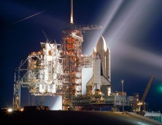 The space shuttle Columbia, NASA's first orbiter, is showered with lights in this nocturnal scene at Launch Pad 39A at the Kennedy Space Center in Cape Canaveral, Fla., during preparations for the first flight (STS-1) of NASA's new reusable spacecraft sys