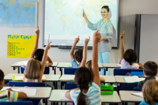 Teacher standing before class pointing to projector screen.