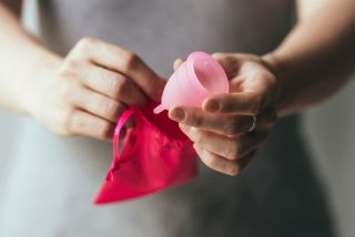 A woman holding a menstrual cup.