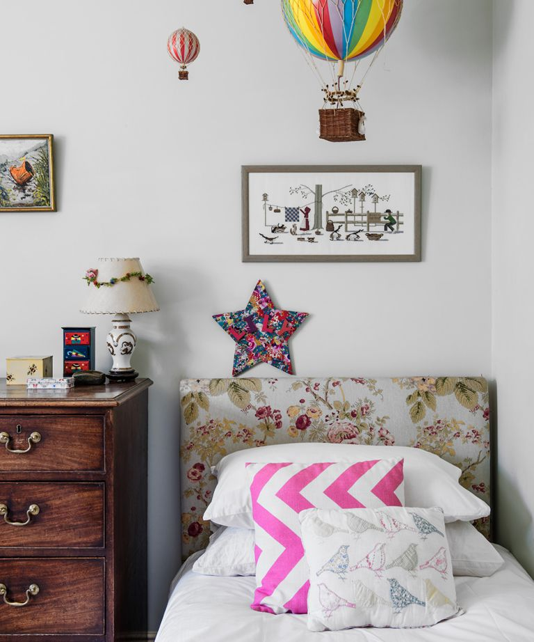 Small bedroom ideas for kids illustrated in a traditional neutral scheme with dark wood vintage drawers and a pale floral headboard.