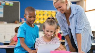 K12 teacher works with two children using an iPad