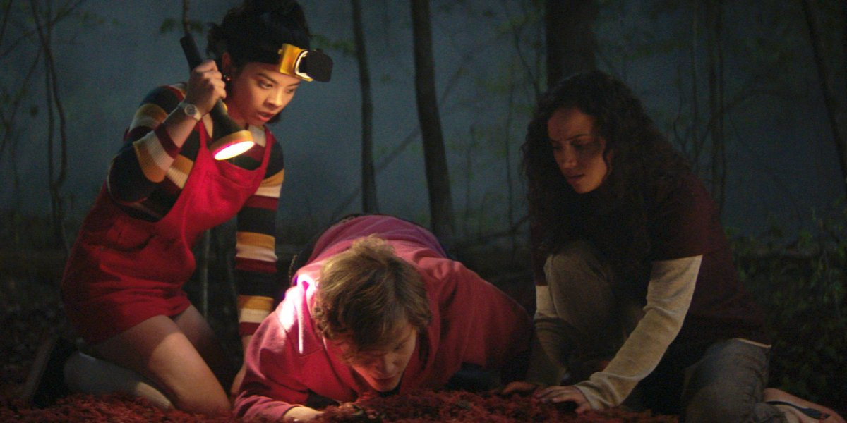 Julia Rehwald, Fred Hechinger, and Kiana Madeira digging in the woods in Fear Street.