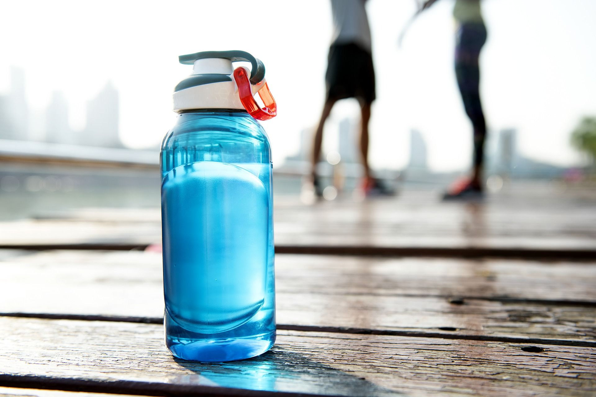Water bottle in foreground of two resting runners