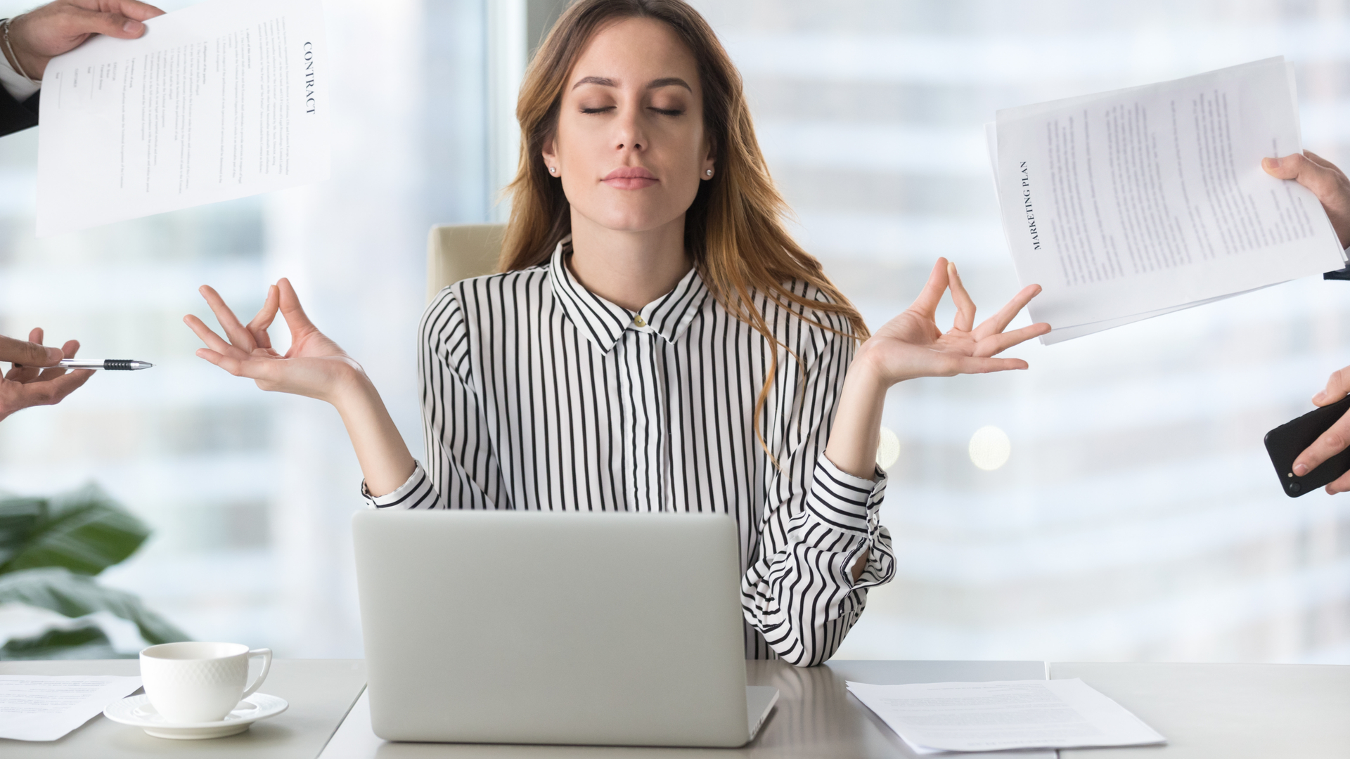 Calm female executive meditating in front of a laptop