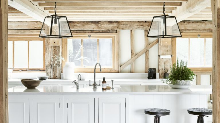 White kitchen island with metal tap in wooden kitchen
