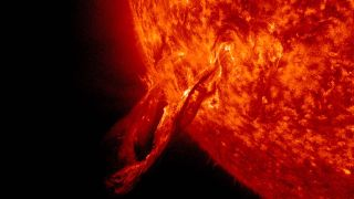 A solar flare that looks like a snake breaks away from the sun and into space