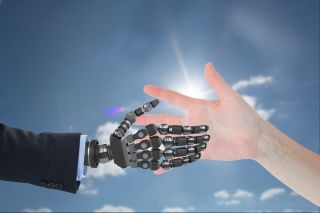 robot hand and human hand against sky background.