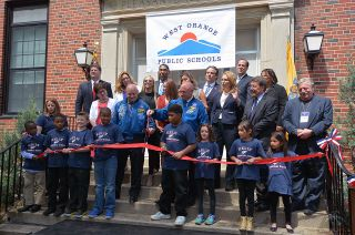 Astronauts Mark and Scott Kelly join students and school officials cutting a ribbon marking the opening of the newly-renamed Kelly Elementary School in West Orange, New Jersey, May 19, 2016.
