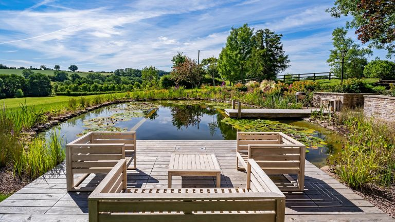 natural pools with wooden deck and seating by Poolscape