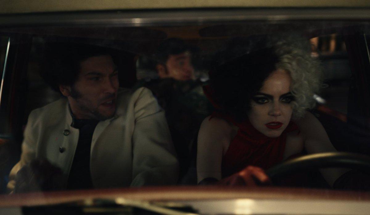 Joel Fry, Paul Walter Hauser, and Emma Stone flee in a stolen car in Cruella.