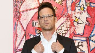 Musician/artist Jason Newsted poses for a photos front of his artwork at VIP Preview for Art New York