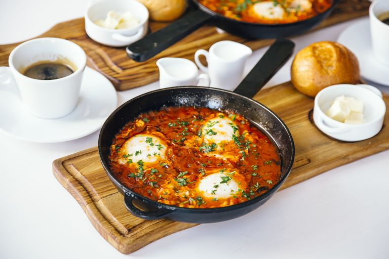 egg recipes: Shakshuka baked eggs on a table with coffee