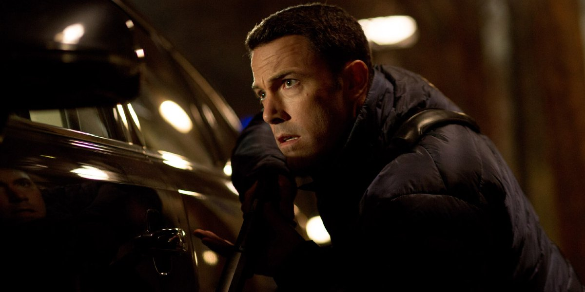 Ben Affleck takes cover behind a car in The Accountant.