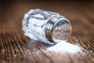 A tipped-over salt shaker with spilled salt.