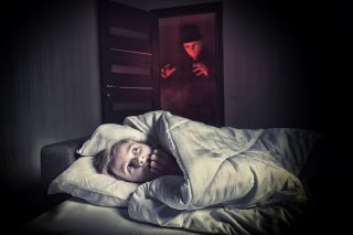 Scared boy lying in the bed while the masked stranger standing in a doorway.