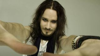 Tuomas Holopainen holding his hands out towards the camera