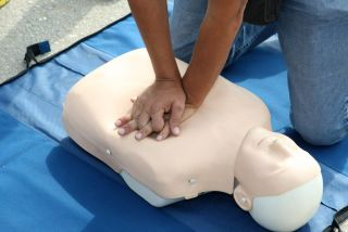 A person practices CPR on a manequin.