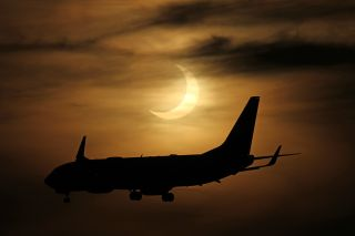 A plane flies in front of the partially eclipse sun in this stunning photo from photographers Imelda Joson and Edwin Aguirre at Black Falcon Cruise Ship Terminal in Boston on June 10, 2021.