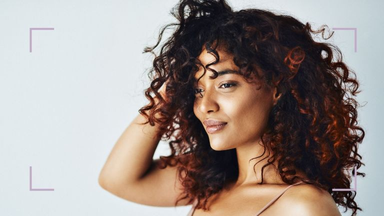 Woman with curly hair learning how to get rid of dandruff