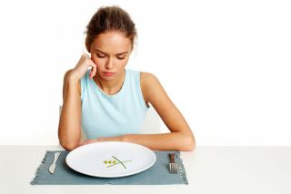 A woman staring at an almost empty plate.