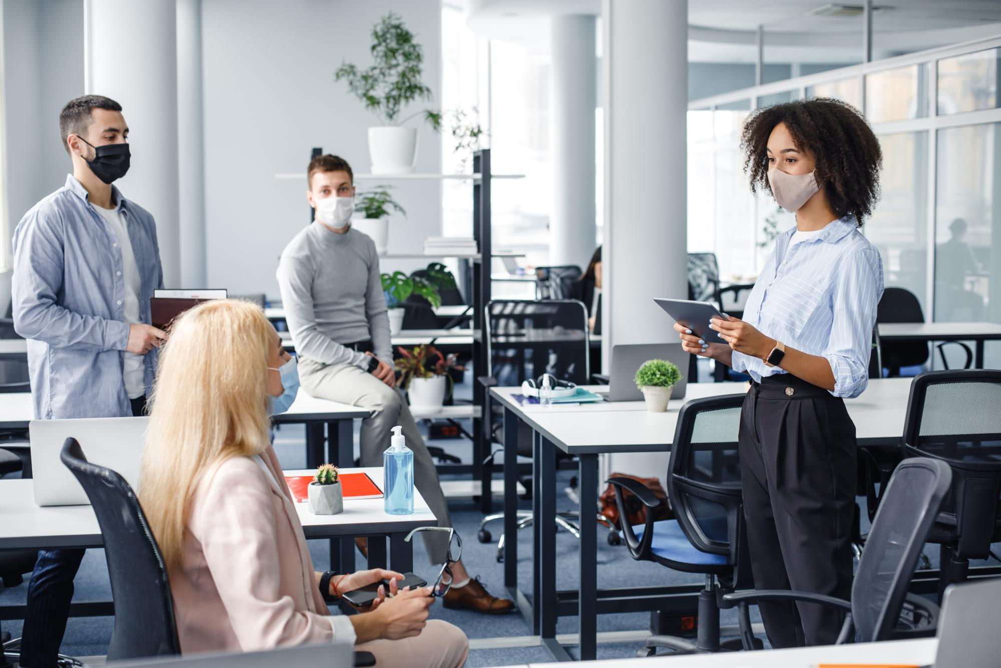 Group of office staff wearing masks in a meeting
