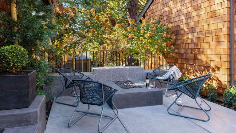 Small back yard landscaping ideas with al fresco dining and a fire pit in a gray paved yard between two brick walls.