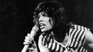 A photograph of Mick Jagger holding a microphone in stage in 1976