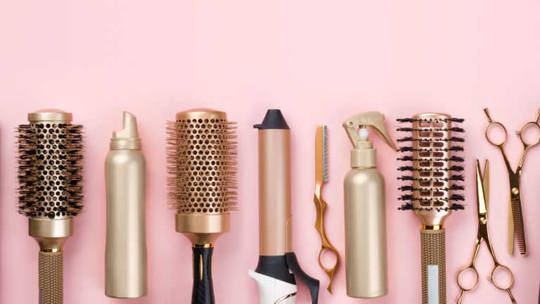 hairdressing and styling tools on pink background