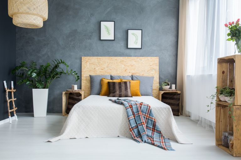 Escapism bedroom with grey walls and colourful pillows nd throws