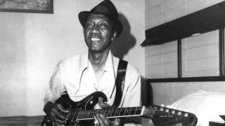 Hound Dog Taylor sitting on a bed and playing guitar