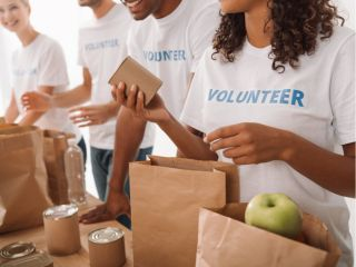 People volunteering to pack food in paper bags