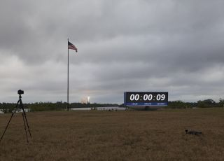 A SpaceX Falcon 9 rocket launches its first cargo mission for NASA from the agency's historic Pad 39A, with a U.S. flag and NASA countdown clock in the foreground, in this view from the Kennedy Space Center in Cape Canaveral, Florida on Feb. 19, 2018.