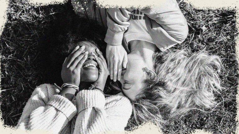 Two best friends telling secrets lying in the grass