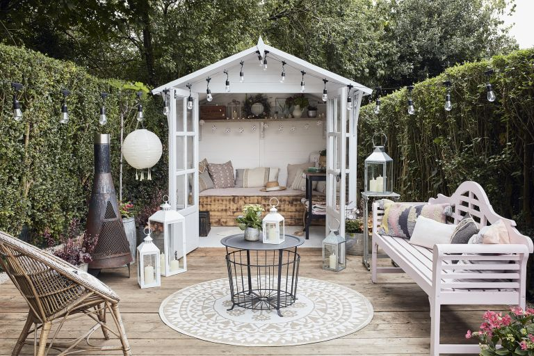 she shed ideas - pretty she shed opening onto an outdoor seating area with cushions, a coffee table, and festoon lights