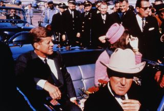 President John F. Kennedy and his wife Jacqueline in a limousine in Dallas shortly before his assassination on Nov. 22, 1963. (Texas Gov. John Connally adjusts his tie in the foreground.)
