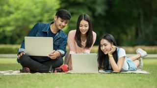 Student software: three students using laptops on lawn